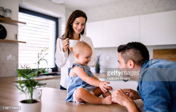 portrait of young couple with toddler girl standing indoors in kitchen at home. - young family stock pictures, royalty-free photos & images