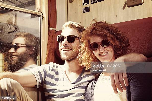 Portrait of young couple with wooden sunglasses sitting in compartment