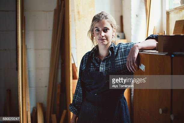 portrait of young craftswoman leaning on cupboard in organ workshop - craftsperson stock pictures, royalty-free photos & images