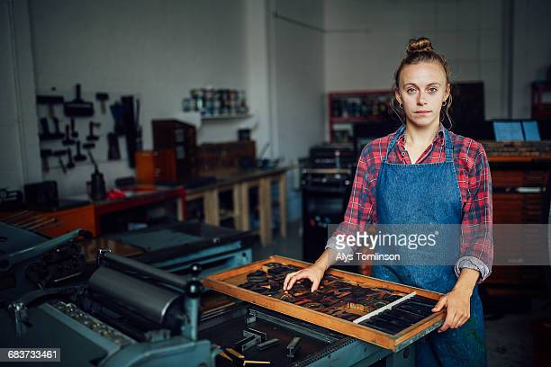 Portrait of young craftswoman next to tray of letterpress letters in print workshop