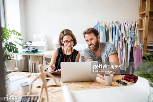 a portrait of young creative couple with laptop indoors making old clothes new and trendy. - adulte d'âge moyen photos et images de collection