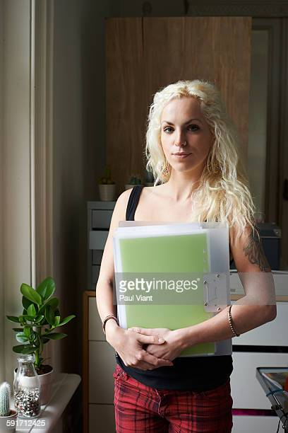 portrait of young creative woman holding file