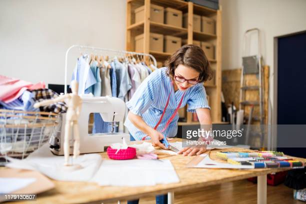 A portrait of young creative woman indoors making old clothes new and trendy.