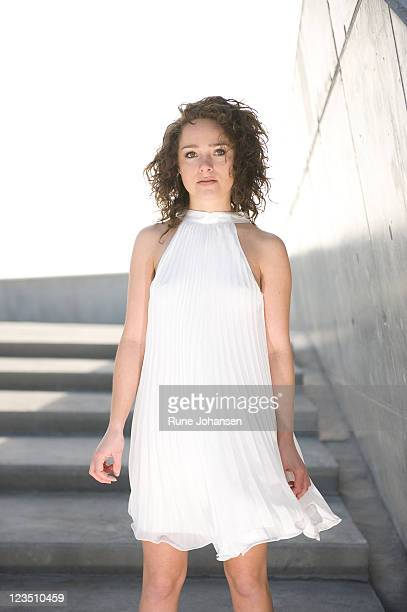 portrait of young danish woman, 26 years old, outdoors in a white cocktail dress at amager strandpark, copenhagen, denmark - 25 29 years stock pictures, royalty-free photos & images