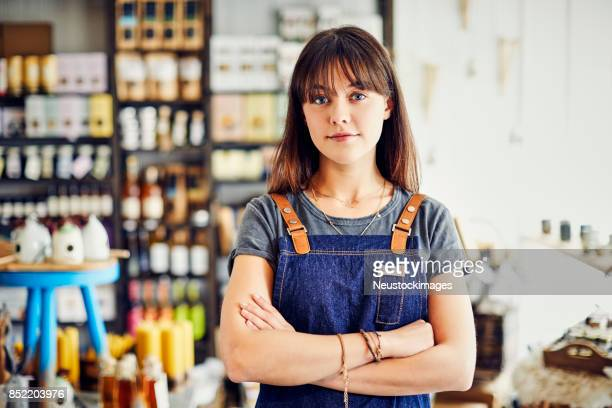 Portrait of young deli owner standing arms crossed in store