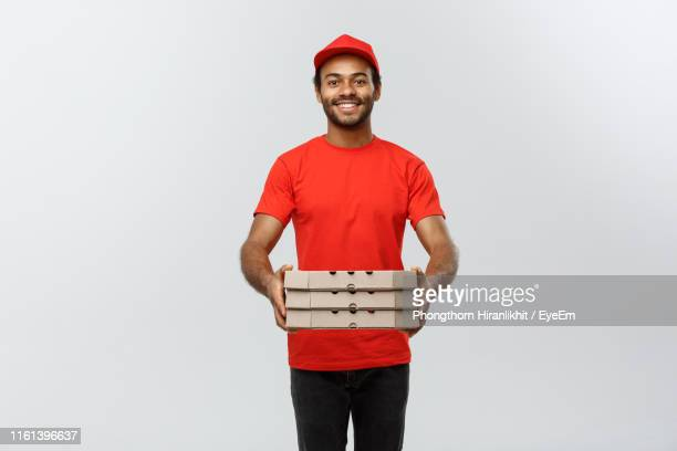portrait of young delivery man holding cardboard box against white background - delivery person stock pictures, royalty-free photos & images