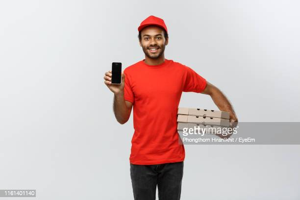 portrait of young delivery man holding cardboard box against white background - cap stock pictures, royalty-free photos & images
