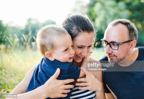 A portrait of young family with a toddler boy sitting outdoors in nature in summer.