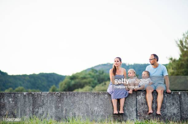 A portrait of young family with two toddler children sitting outdoors on a stone wall in nature in summer.