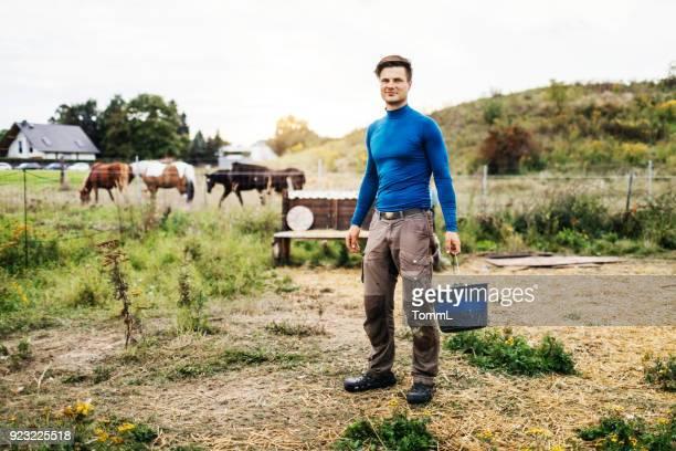 Porträt des jungen Bauern halten Eimer