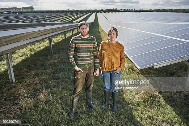 Portrait of young farming couple in solar farm