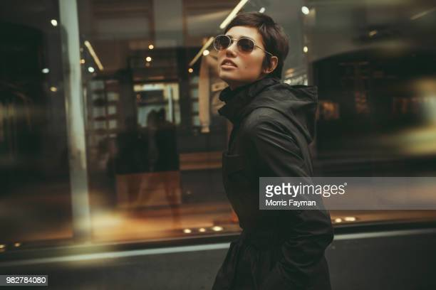 portrait of young fashionable woman walking along window, moscow, russia - fashion stock-fotos und bilder