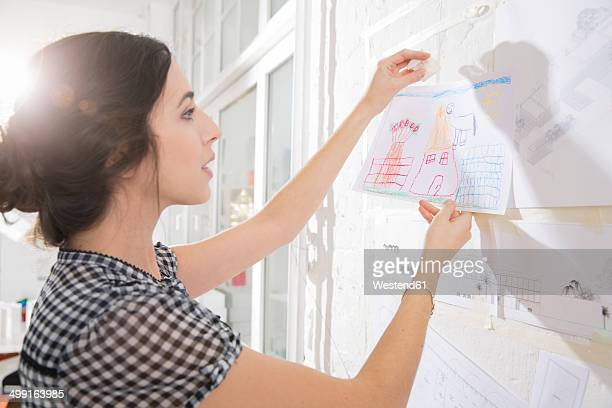Portrait of young female architect fastening child's drawing on pin board