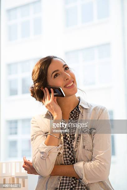 Portrait of young female architect telephoning in office