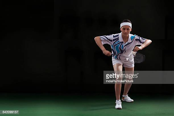 Portrait of young female badminton player ready to serve