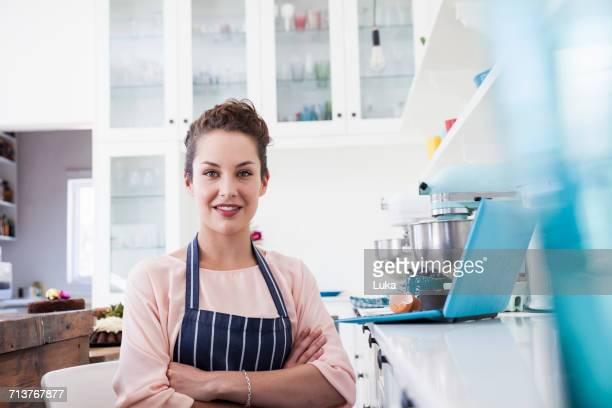 Portrait of young female baker in kitchen