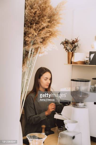 portrait of young female barista in green linen blouse, foaming milk behind the counter in the modern minimalistic coffee shop - pampa stock-fotos und bilder