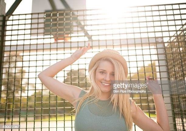 portrait of young female basketball player holding onto wire fence - bethnal green stock pictures, royalty-free photos & images