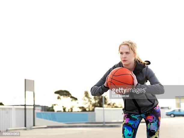 portrait of young female basketball player practicing throw in parking lot - one young woman only stock pictures, royalty-free photos & images