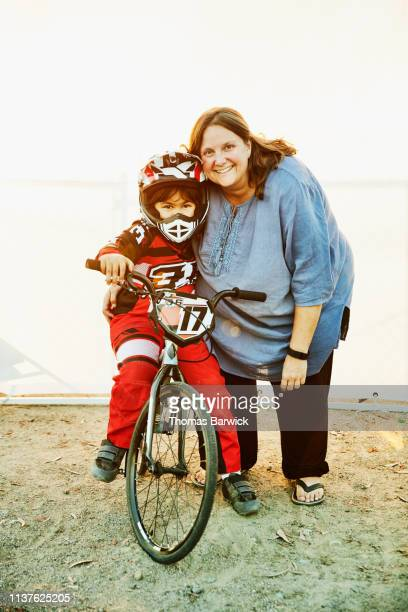 Portrait of young female BMX racer sitting on bike being embraced by mother before race
