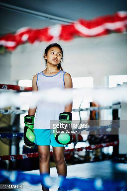 portrait of young female boxer standing in boxing ring during training session - boxing shorts stock pictures, royalty-free photos & images