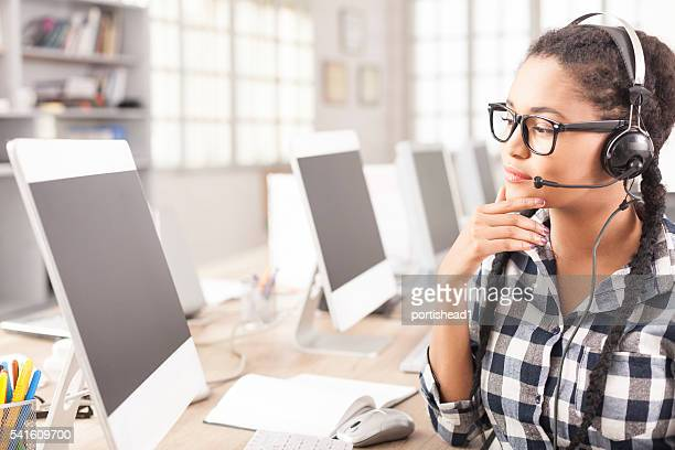 Portrait of young female call center operator with headphones