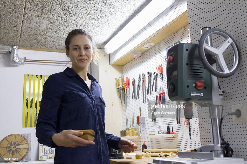 Portrait of young female carpenter at workbench in workshop : Stock-Foto