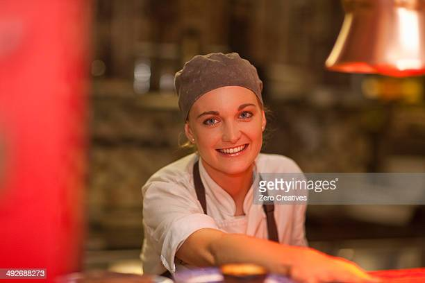 Portrait of young female chef serving over cafe counter