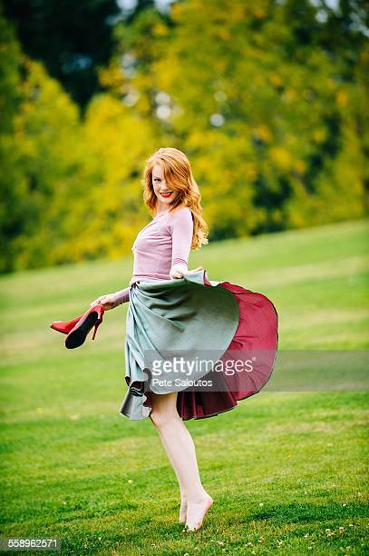 Portrait of young female dancer poised holding skirt and red high heels in park