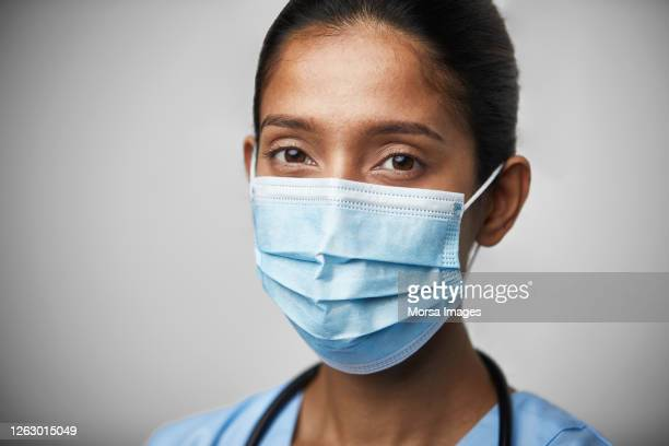 portrait of young female doctor with surgical face mask. - essential workers stock pictures, royalty-free photos & images