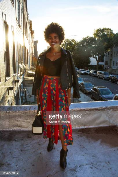 portrait of young female fashion blogger on sunlit terrace, new york, usa - black skirt stock photos and pictures