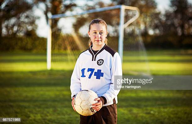 Portrait of young female footballer on pitch