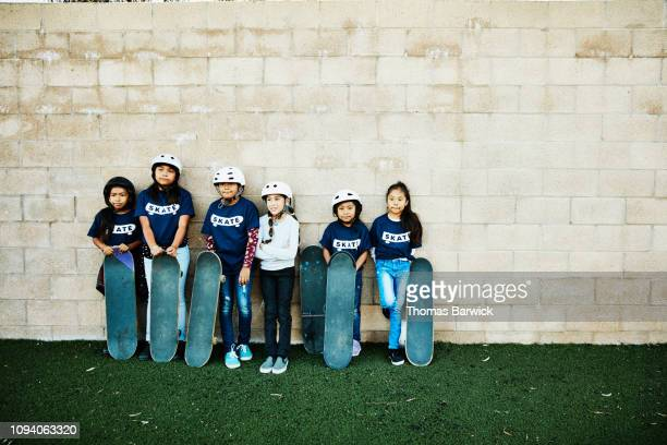 Portrait of young female friends at skateboarding camp