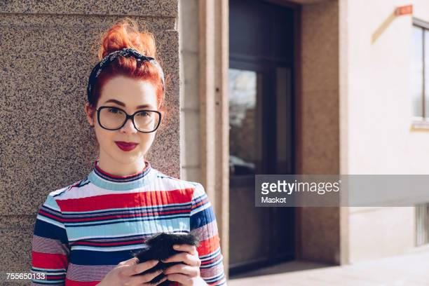 Portrait of young female hipster holding mobile phone while standing against wall