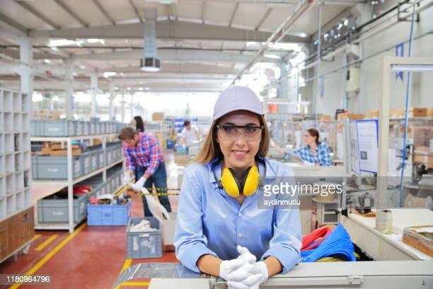 porträt einer jungen industriearbeiterin in der fabrik - weibliche angestellte stock-fotos und bilder