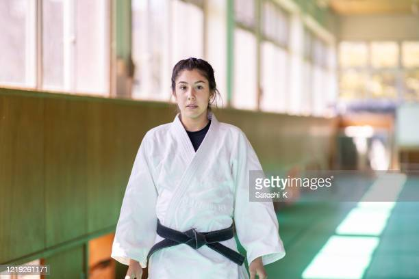 portrait of young female judo athlete in dojo - judo stock pictures, royalty-free photos & images