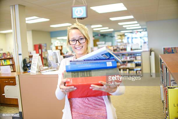 Portrait of young female librarian carrying pile of books