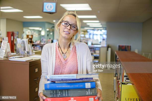 Portrait of young female librarian carrying stack of books