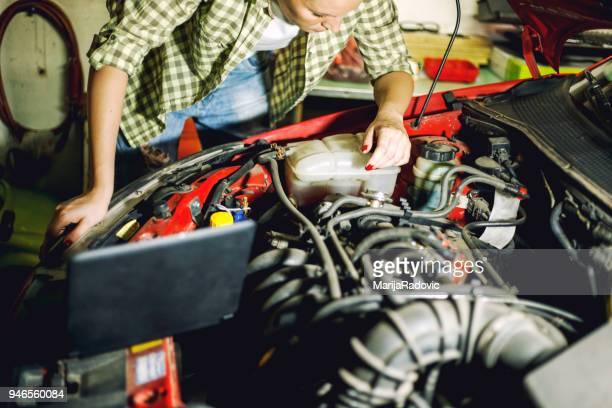 Portrait of  young female mechanic repair car in auto repair shop