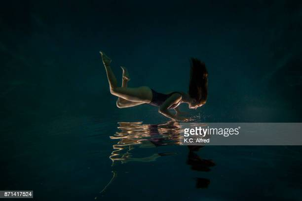 Portrait of young female model underwater in swimming pool.