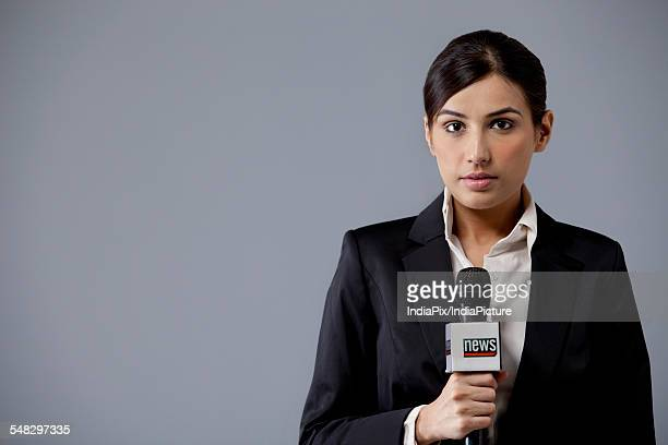Portrait of young female newscaster against colored background