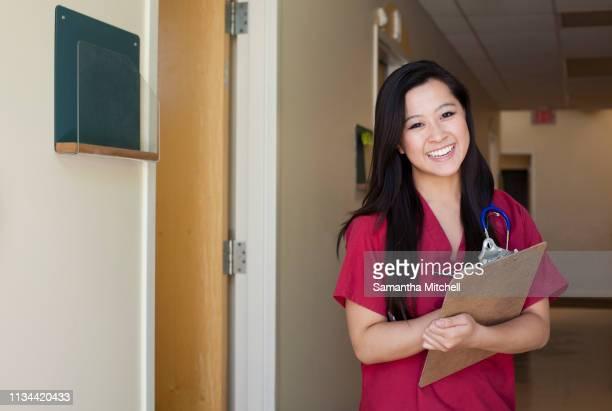 portrait of young female nurse with clipboard - bordeaux rosso foto e immagini stock