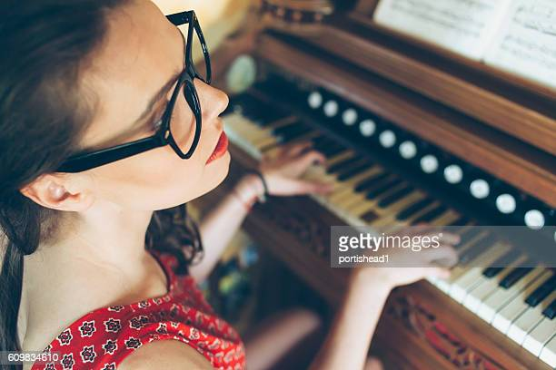 Portrait of young female pianist practicing at home