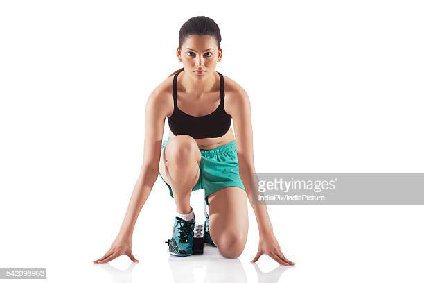 Portrait of young female runner at starting block isolated over white background