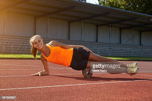 Portrait of young female runner balancing on side at race track