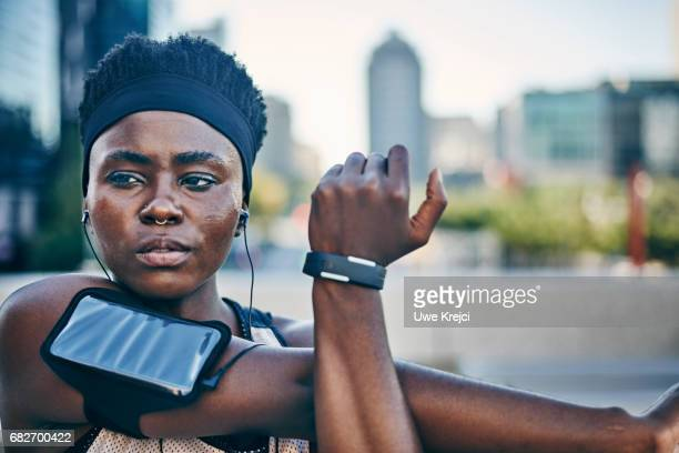 portrait of young female runner - arm band stock pictures, royalty-free photos & images