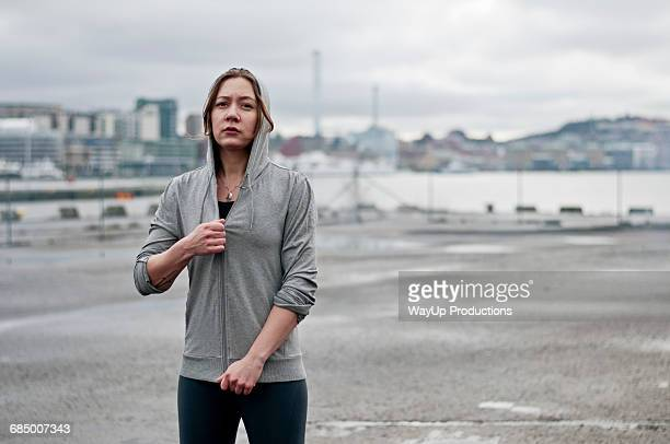 Portrait of young female runner zipping hoody on dockside