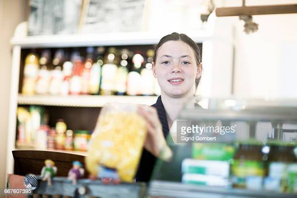 Portrait of young female shop assistant at corner shop counter