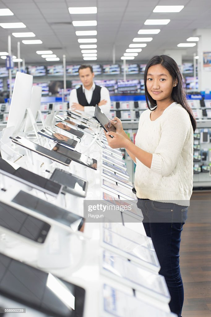 Portrait of young female shopper browsing digital tablets in electronics store : Stock Photo
