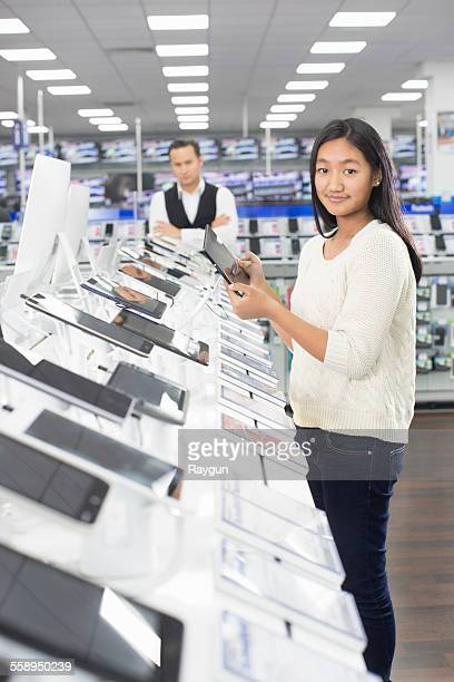 portrait of young female shopper browsing digital tablets in electronics store - electronics store stock photos and pictures